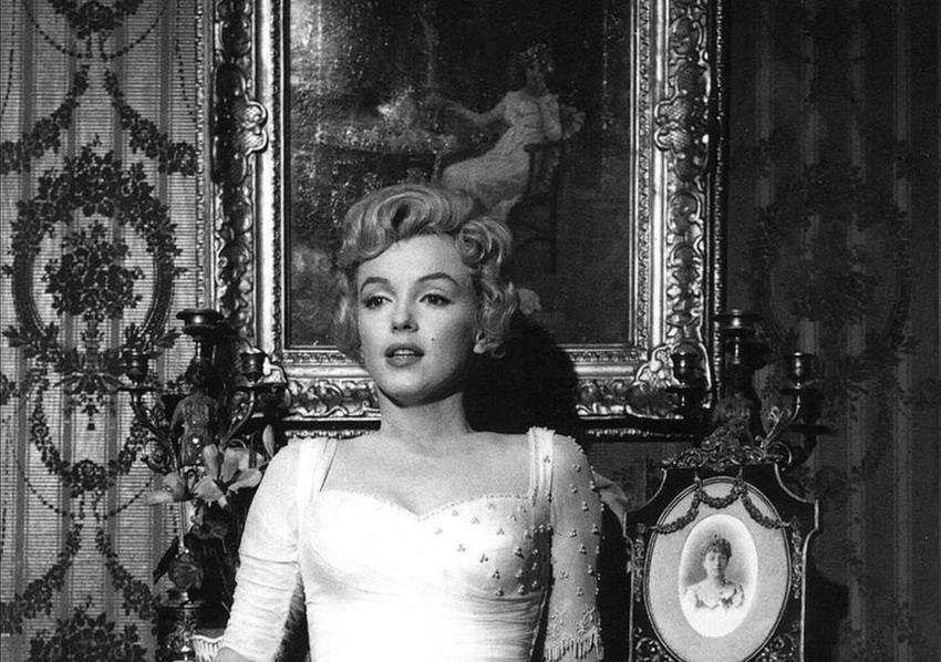 Czarno-białe zdjęcie Marilyn Monroe na tle obrazu, a także życiorys, życie prywatne, filmografia, najważniejsze informacje oraz śmierć