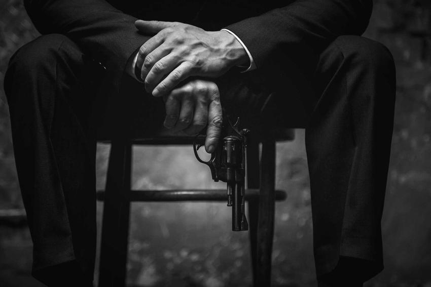 Mężczyzna trzymający w dłoni pistolet siedzący na krześle, a także historia Vito Corleone - słynnego mafioza z Ojca Chrzestnego