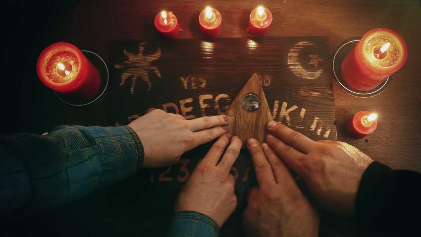 Tablica Ouija w czasie seansu spirytystycznego, a także zasady działania, zasady stosowania, informacje