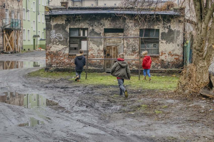 Gromadka dzieci na zabłoconym podwórku przy trzepaku, czyli jak kiedyś bawiły się dzieci